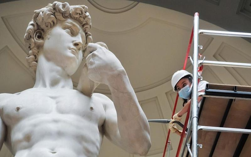 A restorer cleans Michelangelo's David while preparing for the reopening of the Accademia Gallery in Florence - Laura Lezza/Getty