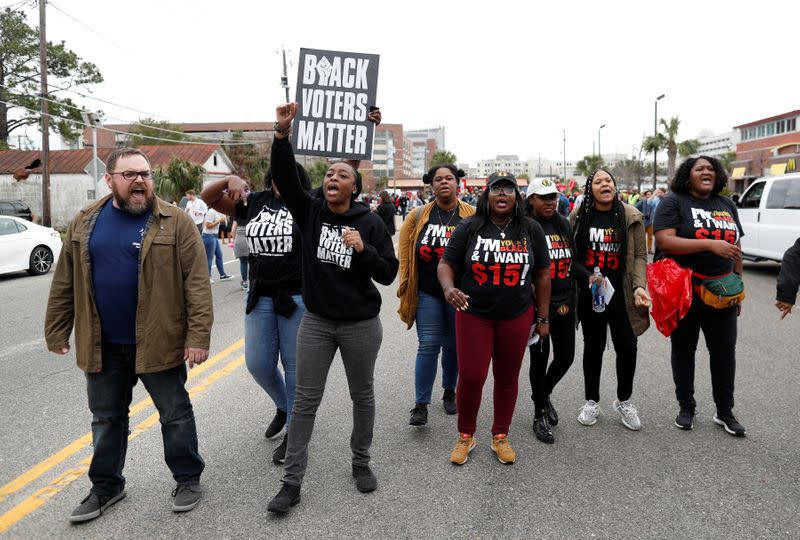 Protestors shout slogans against support of Democratic U.S. presidential candidate and former South Bend Mayor Pete Buttigieg while he leaves from a march for striking McDonald's workers in Charleston