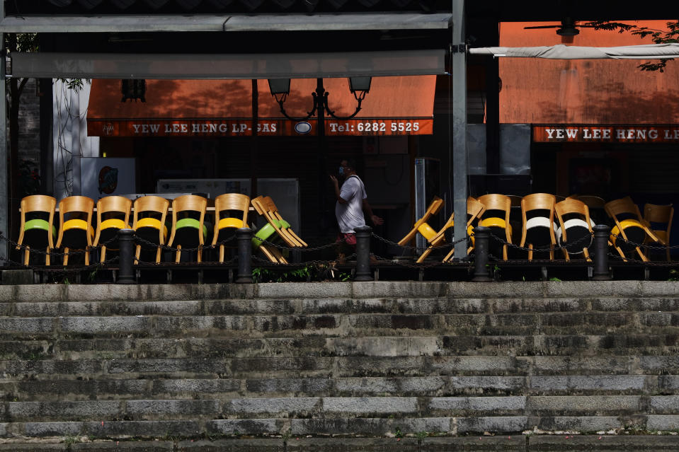 A man wearing protective mask walks past stacked chairs outside a restaurant on May 20, 2021 in Singapore. Singapore enters a month long heightened alert from May 16 to June 13 to curb the spread of COVID-19 cases in the local community. New restrictions on movements and activities have been introduced such as limiting social interaction to two, prohibiting dining out and a reduced operating capacity at shopping malls and attractions. (Photo by Suhaimi Abdullah/NurPhoto via Getty Images)