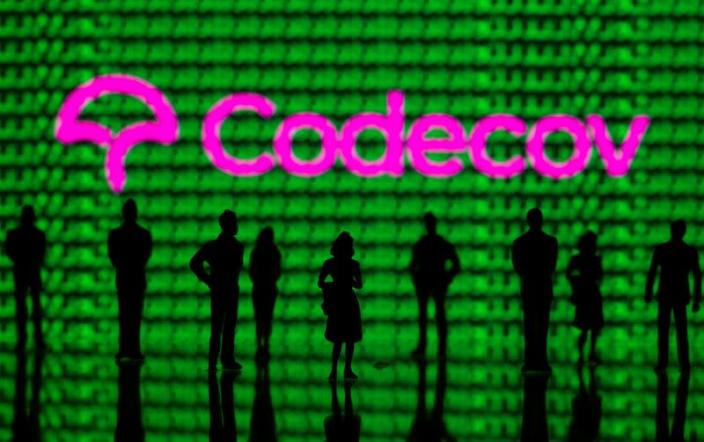 FILE PHOTO: Small toy figures are seen in front of the Codecov logo and cyber binary codes in this illustration