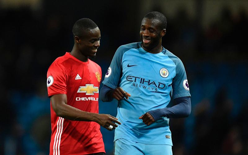 Yaya Toure chats to his compatriot Eric Bailly at the end of the drawn Manchester derby - AFP