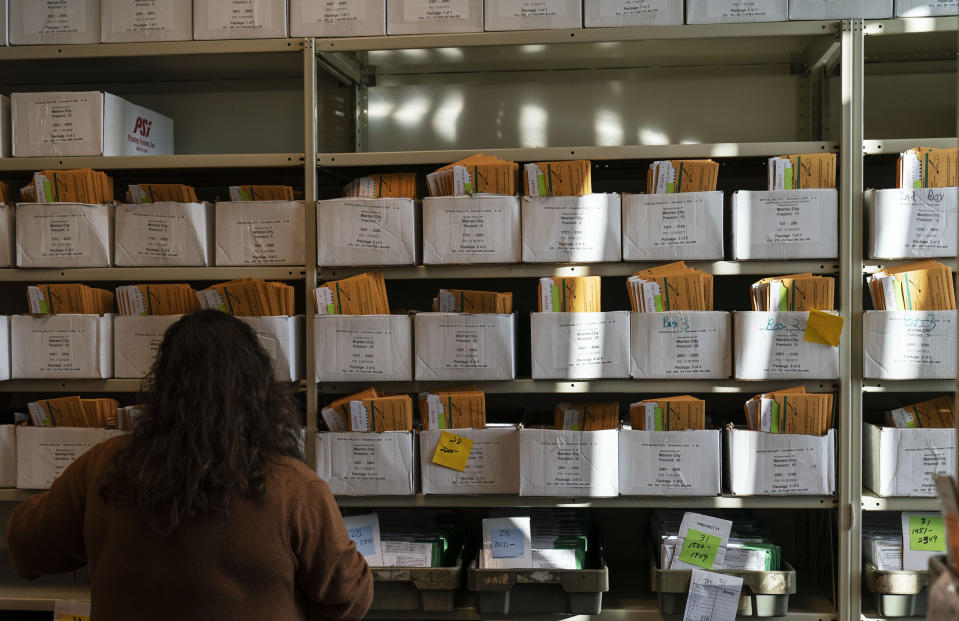 Election worker Madison Takala organizes ballots ahead of Tuesday's general election at the city clerk office in Warren, Mich., Wednesday, Oct. 28, 2020. (AP Photo/David Goldman)