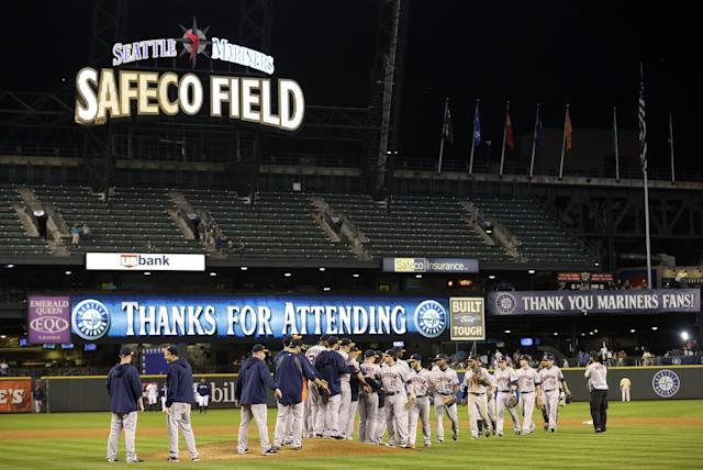 """Nearly empty bleachers are shown above a sign that reads """"Thanks for Attending"""" as Houston Astros players celebrate their 13-2 win over the Seattle Mariners in a baseball game at Safeco Field, Tuesday, Sept. 10, 2013 in Seattle. (AP Photo/Ted S. Warren)"""