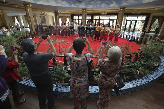 Passengers from the cruise ship Westerdam take a photo of Cambodian dancers after their performance at a hotel in Phnom Penh, Cambodia