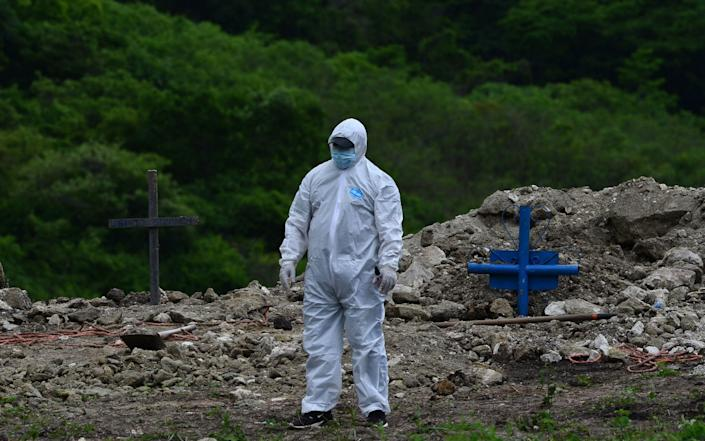A man in a protective suit is pictured after burying a relative who died of Covid-19 on the outskirts of Tegucigalpa - AFP