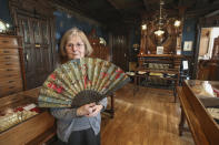 Anne Hoguet, 74, fan maker and director of the hand fan-making museum poses with a a wood roasted hand fan representing the falcon hunt, gouache painting on paper dated from 1880 in Paris, Wednesday, Jan. 20, 2021. The splendid Musee de l'Eventail in Paris, a classed historical monument, is the culture world's latest coronavirus victim. (AP Photo/Michel Euler)