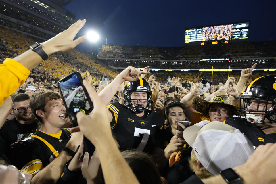 Iowa quarterback Spencer Petras (7) celebrates with fans on the field after Iowa beat Penn State 23-20, in an NCAA college football game, Saturday, Oct. 9, 2021, in Iowa City, Iowa. (AP Photo/Matthew Putney)