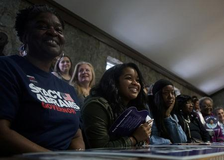 Stacey Abrams supporters smile as they listen as the democratic gubernatorial candidate for Georgia speaks ahead of the midterm elections in Newnan, Georgia, U.S., October 25, 2018. REUTERS/Lawrence Bryant