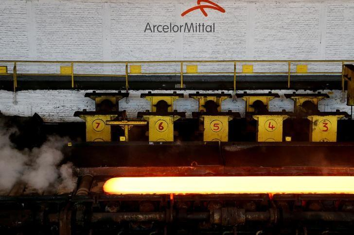 FILE PHOTO - A red-hot steel plate passes through a press at the ArcelorMittal steel plant in Ghent