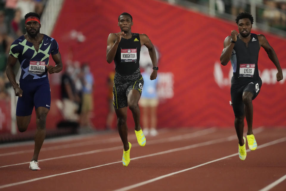 FILE - In this June 27, 2021, file photo, Noah Lyles, right, wins the final in the men's 200-meter run ahead of Kenny Bednarek, left, in second and Erriyon Knighton, in third, at the U.S. Olympic Track and Field Trials in Eugene, Ore. Lyles, the 200-meter world champion, will lead a strong contingent of American sprinters that includes teenager Knighton at the upcoming Tokyo Games. (AP Photo/Ashley Landis, File)