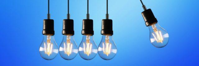 Group of hanging lightbulbs with one offset from the others.