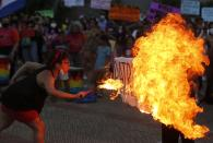 "A fire breather burns a poster with the word ""Patriarchy"" during a march commemorating Women's International Day in Asuncion, Paraguay, Monday, March 8, 2021. (AP Photo/Jorge Saenz)"