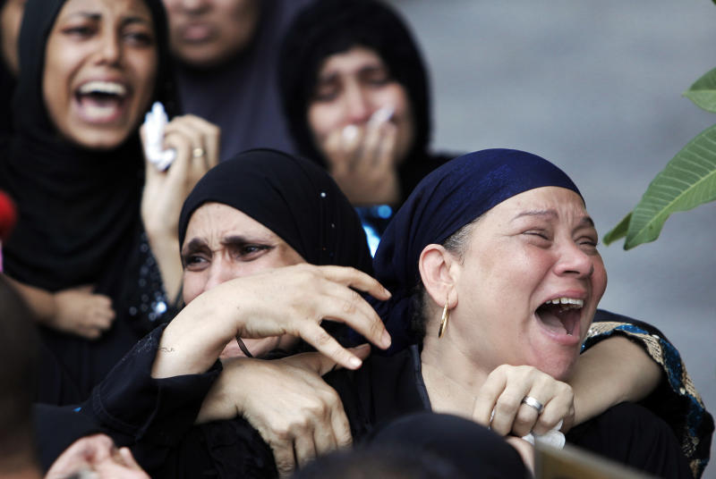 Egyptian women mourn during the military funeral of 16 Egyptian soldiers who were killed Sunday, Aug. 5, 2012 during an attack at a checkpoint along the Sinai border with Israel by Islamic militants with purported ties to Gaza, in Cairo, Egypt, Tuesday, Aug. 7, 2012. Mourners prayed for the dead at a mosque in an east Cairo suburb on Tuesday. The coffins, wrapped in Egypt's red-white-and-black flag, were later taken to a nearby square where a military ceremony is under way. (AP Photo/Amr Nabil)