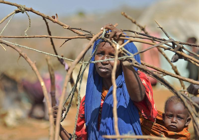 A woman builds a shelter at a makeshift camp on the outskirts of Baidoa, in the southwestern Bay region of Somalia