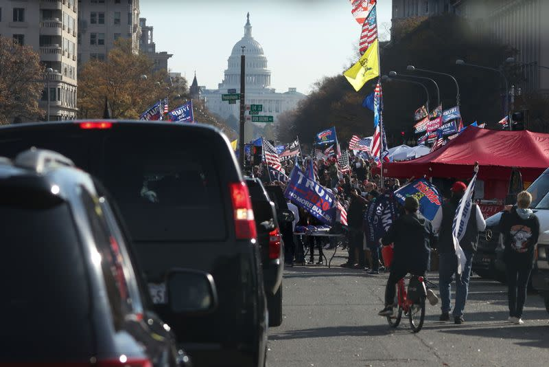 Supporters of President Trump cheer alongside the presidential motorcade at Freedom Plaza near the White House in Washington