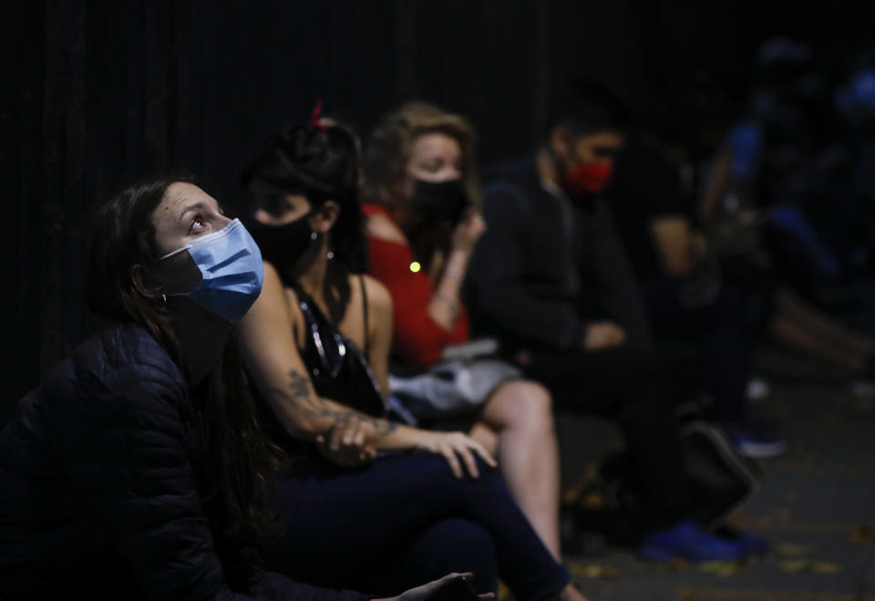 People wait their turn to get tested for COVID-19 outside a hospital in Buenos Aires, Argentina, Thursday, April 8, 2021. Argentina has issued a night-time lockdown starting Friday midnight to try to stop the increase of COVID-19 infections. (AP Photo/Natacha Pisarenko)
