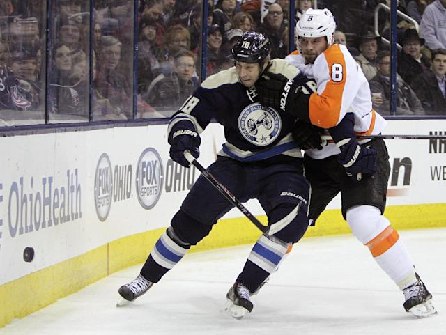Philadelphia Flyers' Nicklas Grossman, right, of Sweden, and Columbus Blue Jackets' RJ Umberger fight for a loose puck during the second period of an NHL hockey game Thursday, Jan. 23, 2014, in Columbus, Ohio. (AP Photo/Jay LaPrete)