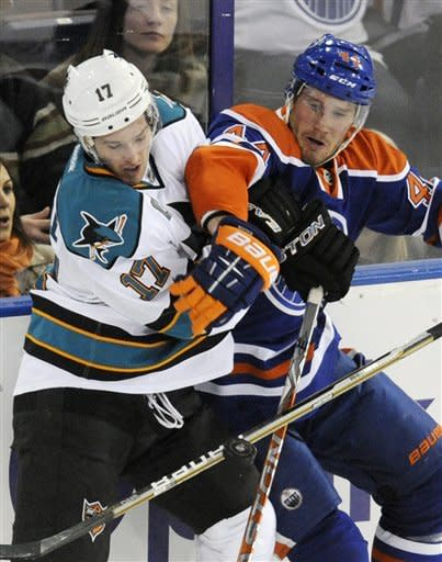 San Jose Sharks' Torrey Mitchell, left, vies for the puck with Edmonton Oilers' Corey Potter during the first period of an NHL hockey game in Edmonton, Alberta, on Monday, March 12, 2012. (AP Photo/The Canadian Press, John Ulan)