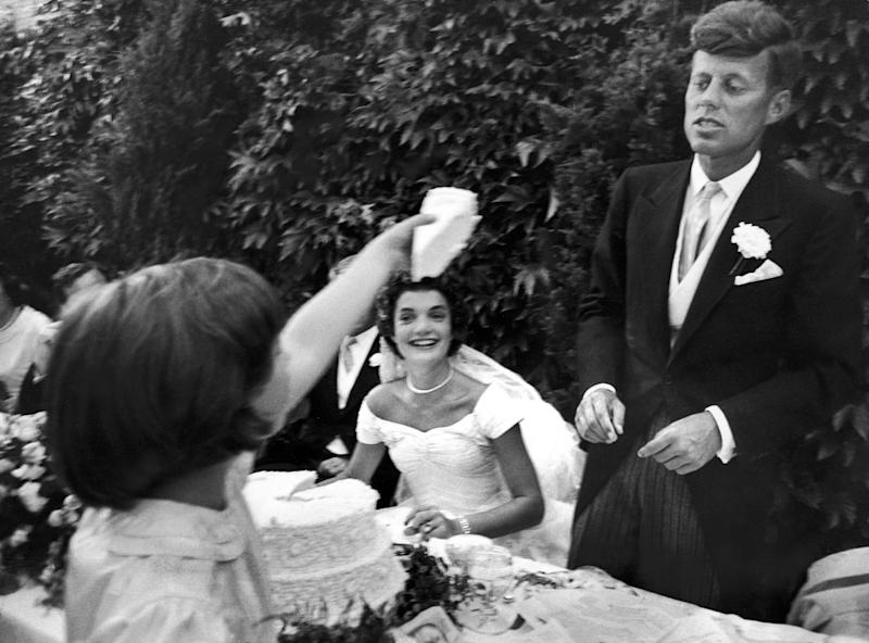 Flower girl Janet Auchincloss holding up a wedge of wedding cake for bridegroom Sen. John Kennedy as her half-sister bride Jacqueline Bouvier Kennedy looks on in amusement at table during formal luncheon at their wedding reception at her mother's estate. (Photo by Lisa Larsen/Time Life Pictures/Getty Images)