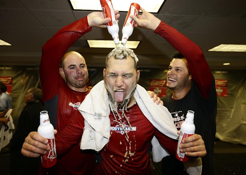 Members of the St. Louis Cardinals celebrate in the locker room after Game 5 of the National League division baseball series against the Washington Nationals on Saturday, Oct 13, 2012, in Washington. St. Louis won 9-7. (AP Photo/Alex Brandon)