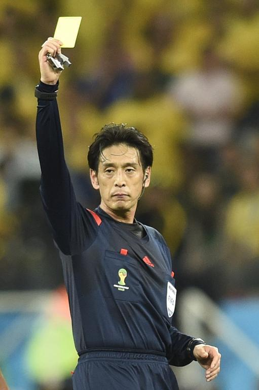 Japanese referee Yuichi Nishimura shows the yellow card during the World Cup opening match between Brazil and Croatia at the Corinthians Arena in Sao Paulo on June 12, 2014