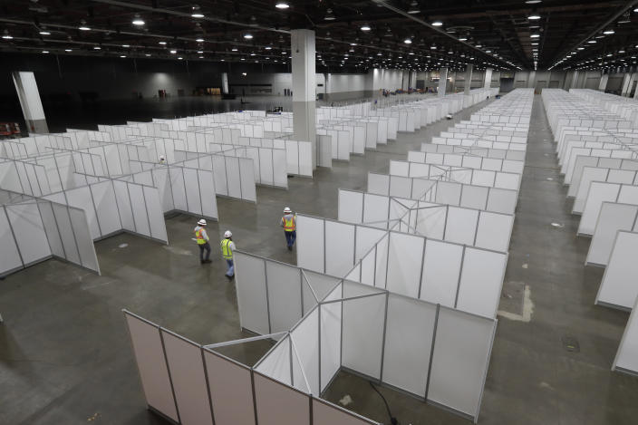 In this April 1, 2020, photo the interior of the TCF Center with temporary hospital rooms is seen inside the convention center in Detroit. In the decade before Michigan and its largest city became the latest hotspot for the deadly coronavirus, officials were steadily cutting back on their first line of defense against pandemics and other health emergencies. Approaching bankruptcy, Detroit disbanded most of its public health department and handed its responsibilities to a private nonprofit. (AP Photo/Carlos Osorio)
