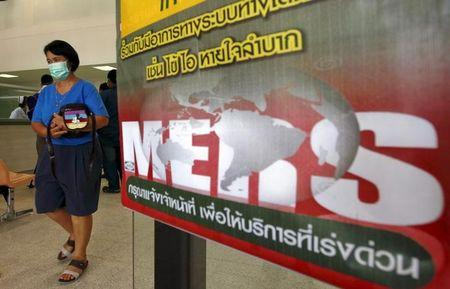 A woman wearing a mask walks past an information banner on MERS at the entrance of Bamrasnaradura Infectious Diseases Institute in Nonthaburi province