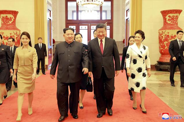 <p>North Korean leader Kim Jong Un and wife Ri Sol Ju, and Chinese President Xi Jinping and wife Peng Liyuan walk together in Beijing, China, in this undated photo released by North Korea's Korean Central News Agency (KCNA) in Pyongyang March 28, 2018. (Photo: KCNA/via Reuters) </p>