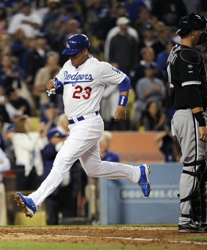 Los Angeles Dodgers' Bobby Abreu, left, scores on a single by James Loney as Chicago White Sox catcher A.J. Pierzynski looks on during the third inning of their baseball game, Saturday, June 16, 2012, in Los Angeles. (AP Photo/Mark J. Terrill)