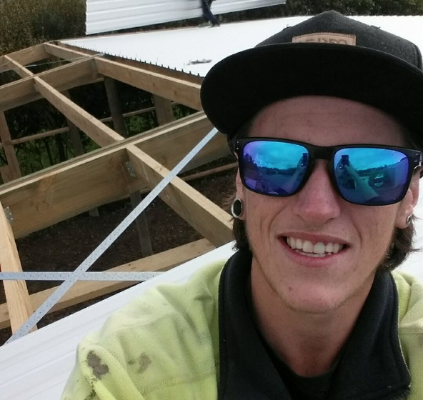 pictured is Jack Lane in sunglasses on a roof while working.