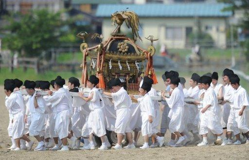 People carry a portable shrine during a parade at the annual Soma Nomaoi festival in Minamisoma, Fukushima Prefecture, on July 28. On Saturday its street came alive with locals galloping triumphantly on horses around a specially-built hippodrome for the three-day festival