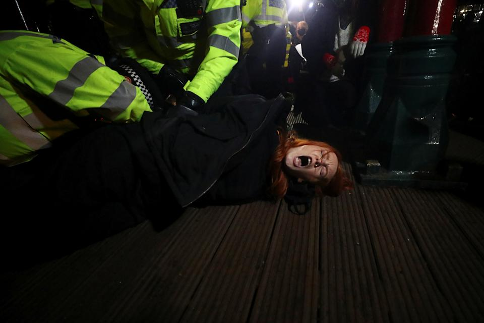Police detain a woman as people gather at a memorial site in Clapham Common Bandstand, following the kidnap and murder of Sarah Everard, in London, Britain March 13, 2021. REUTERS/Hannah McKay