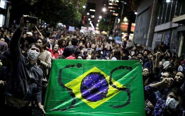 PHOTO: Protesters hold a Brazilian flag with the letters SOS written on it during a demonstration to demand for more protection for the Amazon rainforest, in Sao Paulo, Brazil, on Friday, Aug. 23, 2019. (Nacho Doce/Reuters)