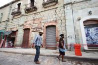 People walk past a building damaged during a quake, in Oaxaca