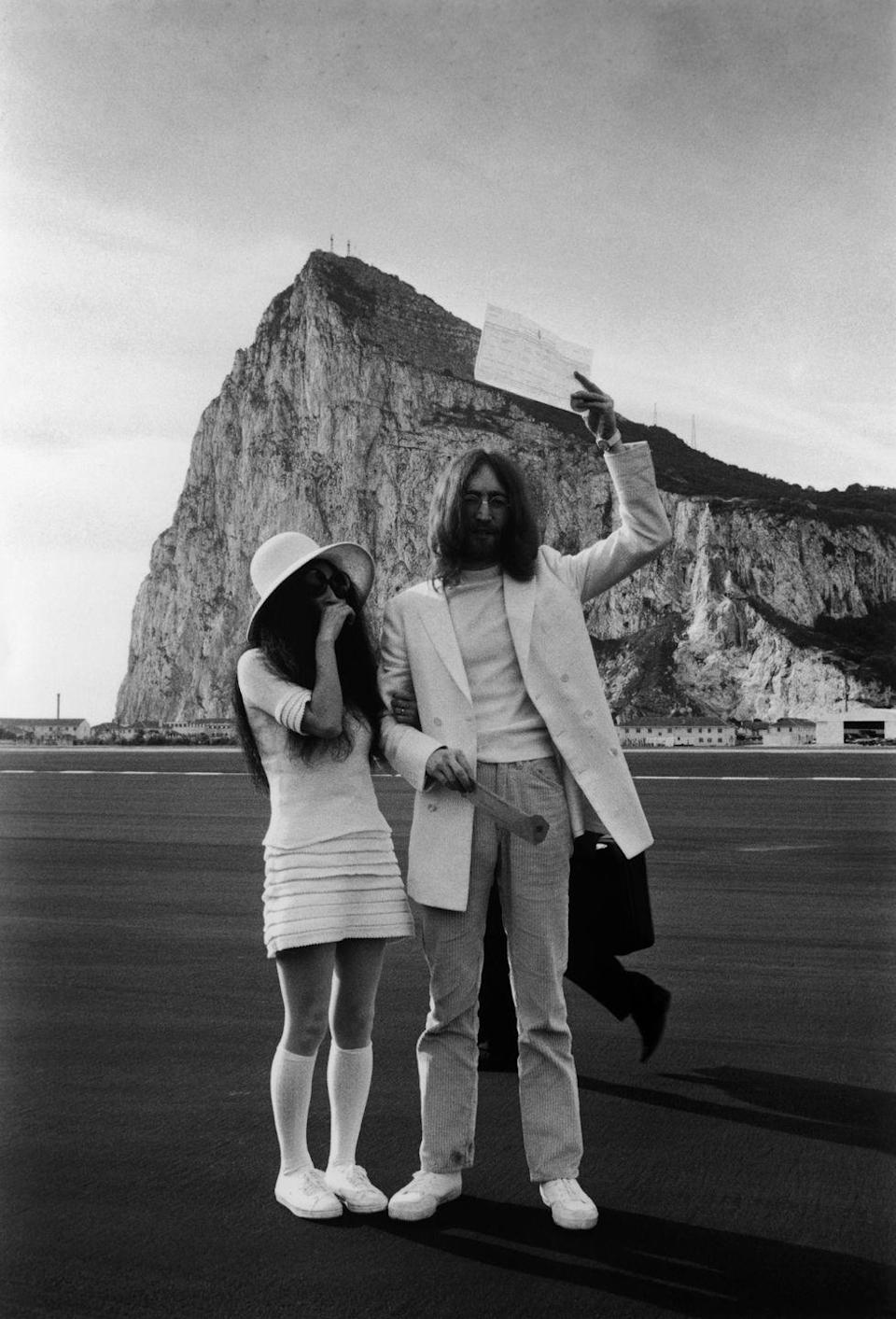 <p>With no other fanfare besides both wearing all white, John Lennon and Yoko Ono hold up their marriage certificate at the airport in Gibraltar to showcase their recent vows.</p>