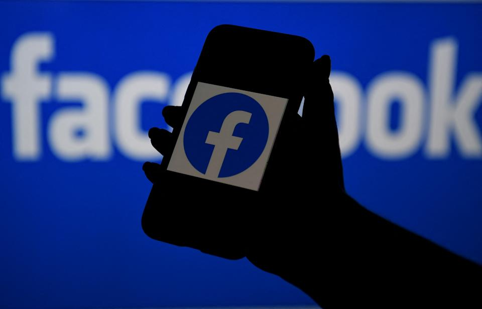 In this photo illustration, a smart phone screen displays the logo of Facebook on a Facebook website background, on April 7, 2021, in Arlington, Virginia - Facebook usage has held steady in the United States despite a string of controversies about the leading social network, even as younger users tap into rival platforms such as TikTok, a survey showed Wednesday. (Photo by OLIVIER DOULIERY / AFP) (Photo by OLIVIER DOULIERY/AFP via Getty Images)