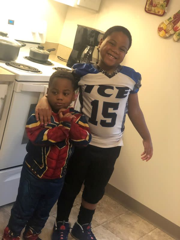 Shanell McGee's sons, 8 year-old DaMir Coleman and 4 year-old KyMir Coleman, stand beside their oven that they use for heat, in Columbus, Ohio