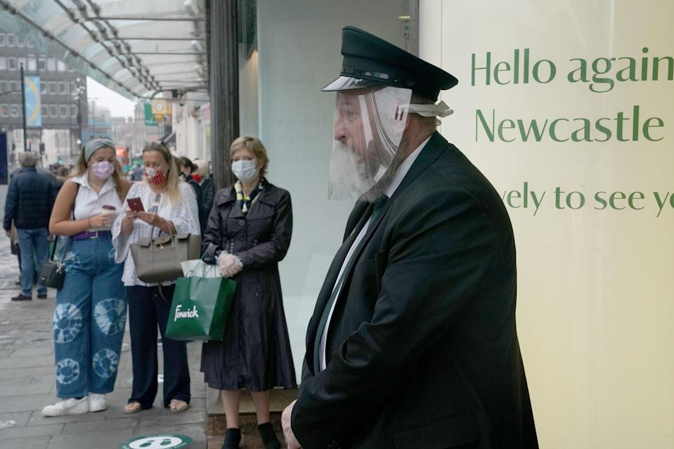 A doorman in a face mask waits to welcome back customers to the Fenwick store in Northumberland Street, Newcastle (PA)