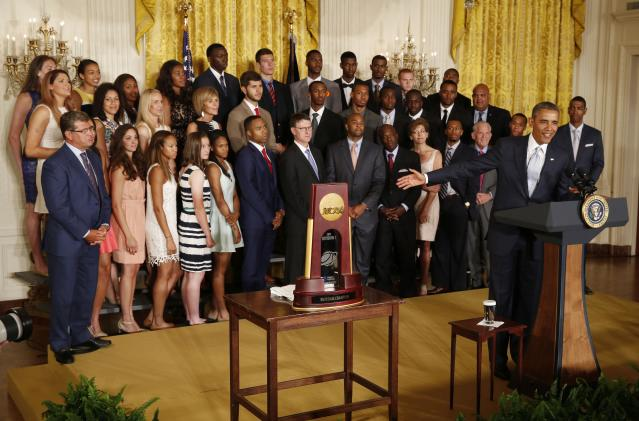 U.S. President Barack Obama honors team members of the 2014 NCAA champion UConn Huskies men's and women's basketball teams after receiving team jerseys while in the East Room of the White House in Washington, June 9, 2014. REUTERS/Larry Downing (UNITED STATES - Tags: POLITICS SPORT BASKETBALL)