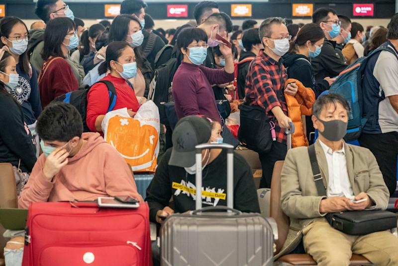 Travellers wearing face masks wait at the departure hall of West Kowloon Station in Hong Kong, China. Source: Getty