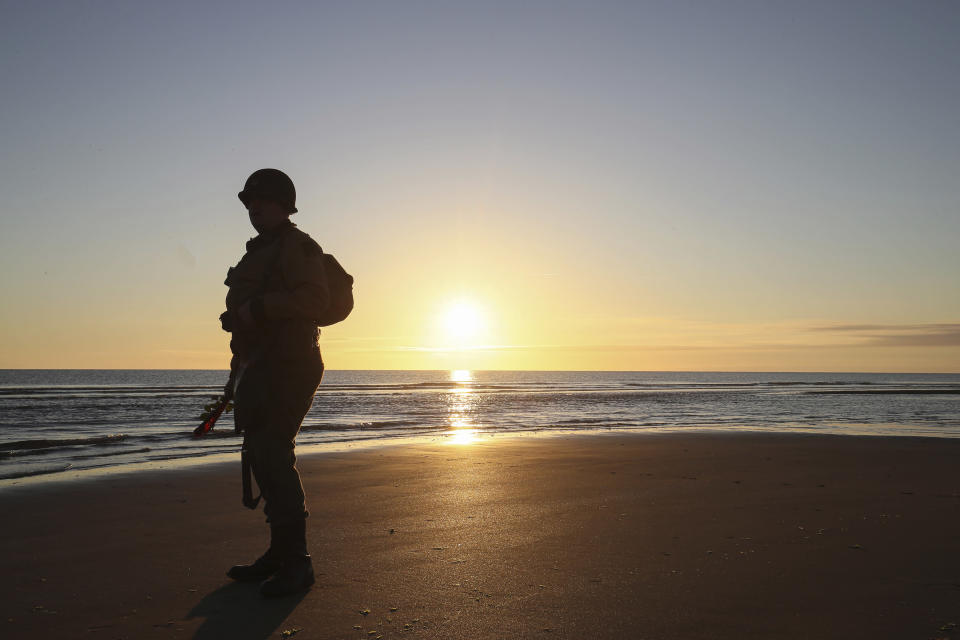 World War II enthusiast stands on the beach at dawn on Omaha Beach, Normandy, Sunday, June 6, 2021, the day of 77th anniversary of the assault that helped bring an end to World War II. While France is planning to open up to vaccinated visitors starting next week, that comes too late for the D-Day anniversary. So for the second year in a row, most public commemoration events have been cancelled. (AP Photo/David Vincent)