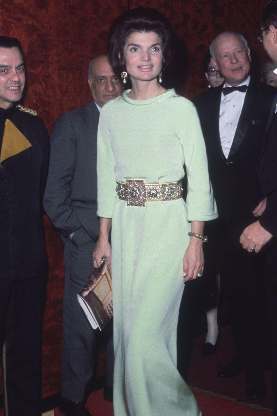<p>As we head into the late '60s, Kennedy begins to embrace longer, leaner silhouettes. This gilded belt lends major glamour factor to her mint gown.</p>