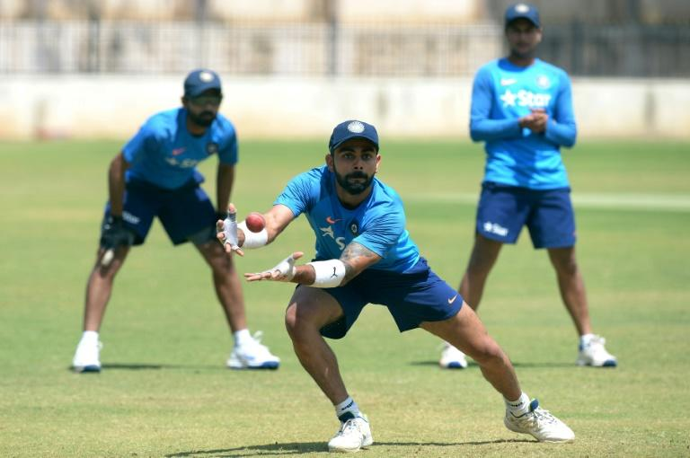 Indian Test captain Virat Kohli takes a catch during a practice session at The M. Chinnaswamy Stadium in Bangalore, on March 1, 2017