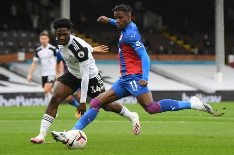 Fulham defender Ola Aina fails to prevent Crystal Palace winger Wilfried Zaha (R) unleashing a shot
