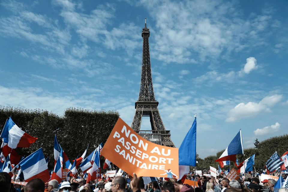 """A protester holds a placard reading """"No to the health pass"""" during a demonstration against the health pass in front of the Eiffel Tower, in Paris, Saturday, Sept. 4, 2021. (AP Photo/Thibault Camus)"""