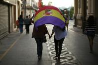 Women hold hands while they walk holding a Republican flag after taking part in an anti-royalist demonstration in Ronda, near Malaga, southern Spain, June 2, 2014. Spain's King Juan Carlos said on Monday he would abdicate in favour of his son Prince Felipe, aiming to revive the scandal-hit monarchy at a time of economic hardship and growing discontent with the wider political elite. REUTERS/Jon Nazca (SPAIN - Tags: POLITICS ROYALS CIVIL UNREST)