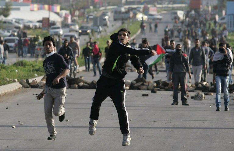 Palestinian protestors hurl stones towards Israeli security forces during clashes at the entrance of the Jalama checkpoint, near the West Bank city of Jenin, on February 24, 2013. Israel demanded Palestinian leaders quell unrest as protests and clashes rocked the West Bank on Sunday, after the death of a prisoner who the Palestinians claim died under Israeli torture