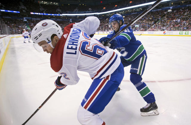 Vancouver Canucks' Elias Pettersson, back right, of Sweden, checks Montreal Canadiens' Artturi Lehkonen, of Finland, during the first period of an NHL hockey game in Vancouver, British Columbia, Saturday, Nov. 17, 2018. (Darryl Dyck/The Canadian Press via AP)