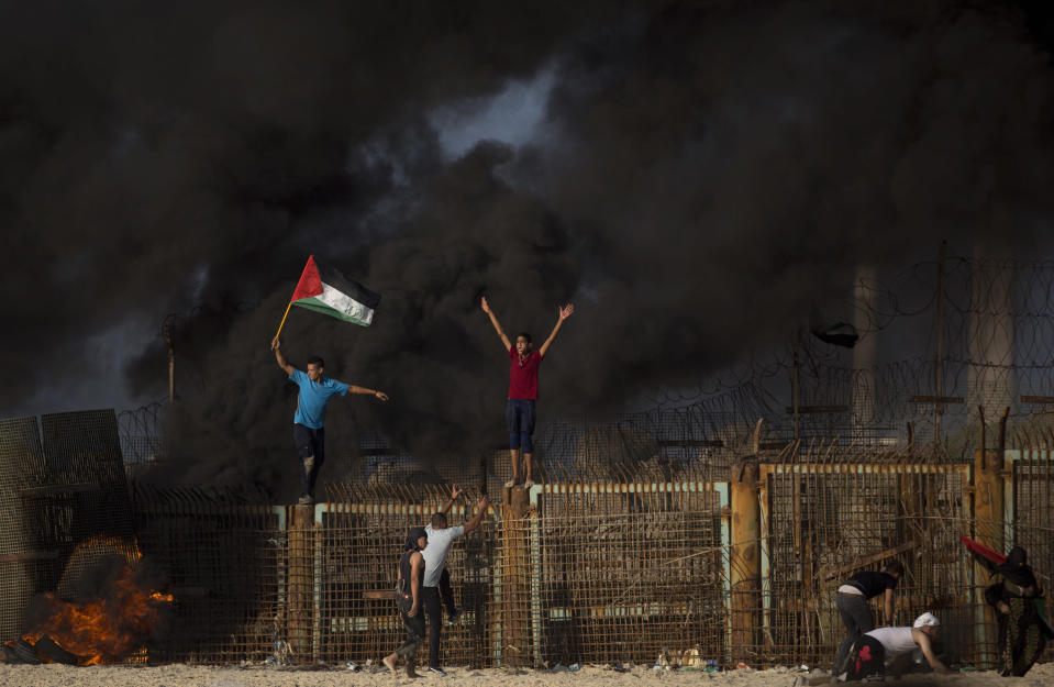 Palestinian protesters climb over the border fence during a protest on the beach at the border with Israel near Beit Lahiya, northern Gaza Strip, Monday, Oct. 15, 2018.(AP Photo/Khalil Hamra)
