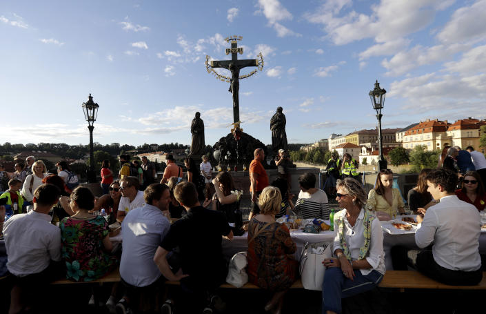 "Residents sit to dine on a 500 meter long table set on the medieval Charles Bridge, after restrictions were eased following the coronavirus pandemic in Prague, Czech Republic, Tuesday, June 30, 2020.<span class=""copyright"">Petr David Josek —AP Photo/Getty Images</span>"